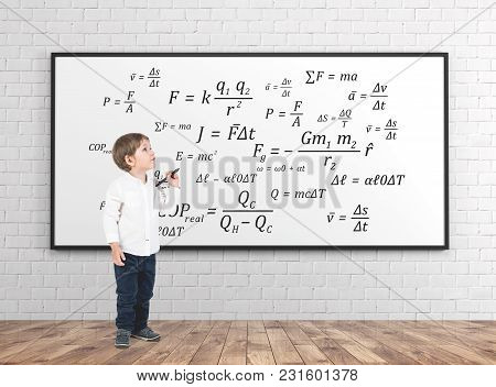 Cute Little Boy In A White Shirt And Dark Jeans Holding A Marker And Looking Upwards. A Whiteboard B