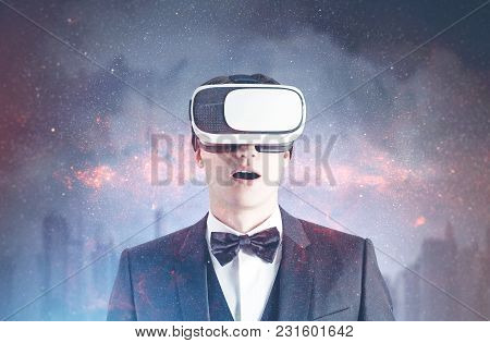 Astonished Young Businessman Wearing A Bowtie And Vr Glasses. Concept Of Future Technology. A Citysc