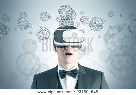 Astonished Young Businessman Wearing A Suit, A Bowtie And Vr Glasses. Concept Of The Future Technolo