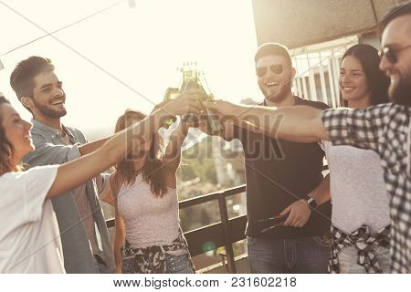 Group Of Young Friends Having Fun At Rooftop Party, Making A Toast With Beer And Enjoying Hot Summer