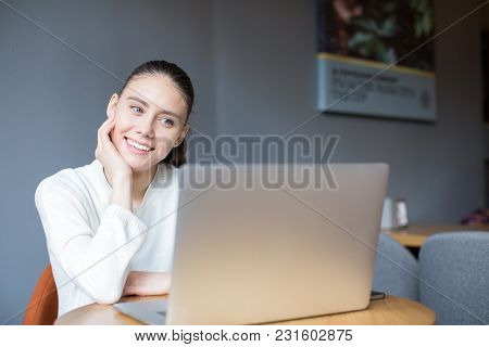 Smiling Woman Having Video Call Via Laptop Computer During Rest In Coffee Shop. Happy Female Watchin