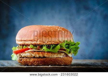 Appetizing Burger With Chicken, Salad And Tomato On A Dark Blue Background.