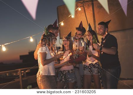 Group Of Young Friends Having A Birthday Party At A Building Rooftop, Singing A Song And Blowing A C