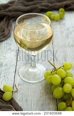 White Wine In A Glass With A Bunch Of Green Grapes Against Grey Wooden Background