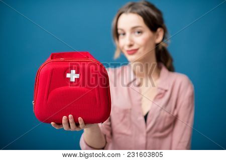 Portrait Of A Woman With First Aid Kit On The Blue Wall Background