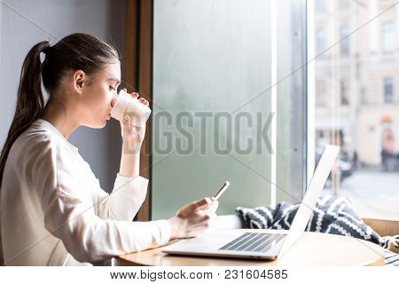 Woman Media Marketer Drinking Latte And Watching Promotional Video On Mobile Phone During Work On La