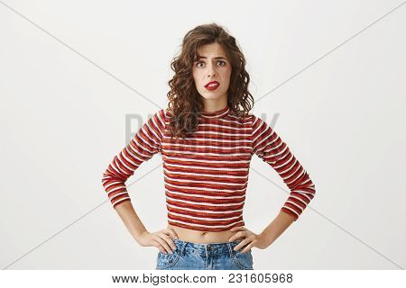 Your Idea Is Very Strange. Portrait Of Good-looking Caucasian Girl Holding Hands On Waist While Look