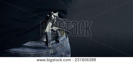 Terrorist Thief Man Holding Gun In His Hand. Hidden Gun. Isolated On Dark Background. Copy Space