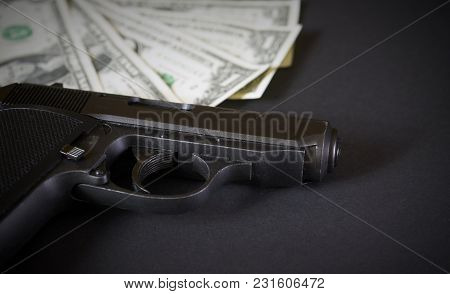 The Gun And Money Concept On Black Table