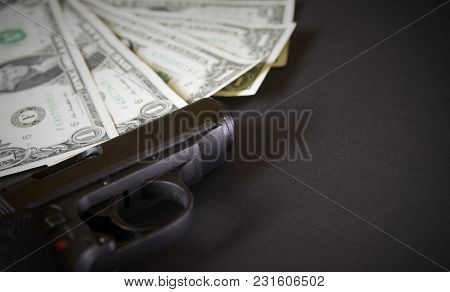 The Gun And Money Concept On Dark Table