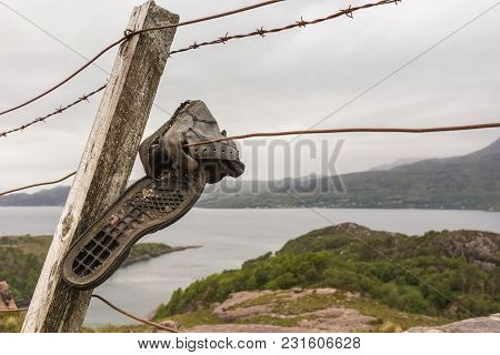 Balgy, Scotland - June 10, 2012: Discarded Trekking Shoes On Barbed Wire Fence With Silver Water Of
