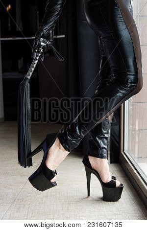 Woman Legs In Leggings And High Heels With Crop Lash. Female Total Leather Black Outfit With Whip.
