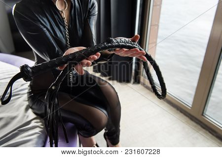 Woman In Total Black Leather Look With Lash In Her Hands. Female Hands Hold Whip.