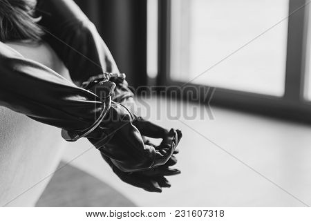 Woman In Bed With Hands In Metal Bracelets In Sunset Light. Black And White Photo.