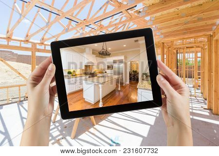 Female Hands Holding Computer Tablet with Finished Kitchen on Screen, Construction Framing Behind.