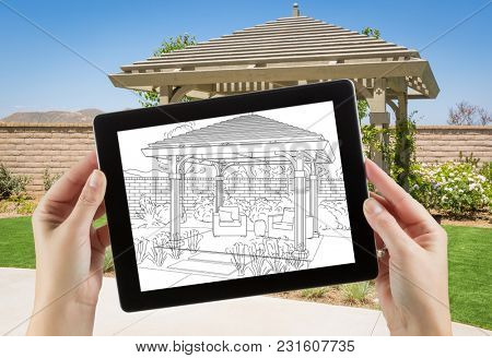 Female Hands Holding Computer Tablet with Drawing of Pergola on Screen, Photo Behind.