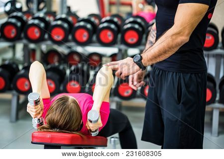 Woman Holding Dumbbell And Trainig Triceps With Trainer In Modern Gym