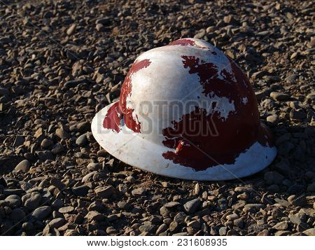 A Construction Hard Hat Left Lying On Gravel, Probably Forgotten By A Construction Worker;