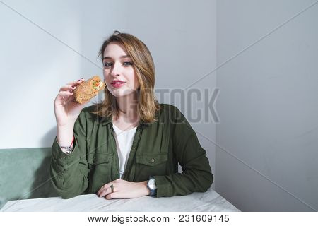 Portrait Of A Beautiful Girl At The Table And With A Sandwich In Her Hands. A Girl With A Beturbist
