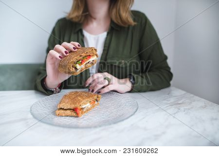 An Appetizing Sandwich In The Hands Of A Young Girl. Sandwich In Close-up And In Focus. The Girl Dis