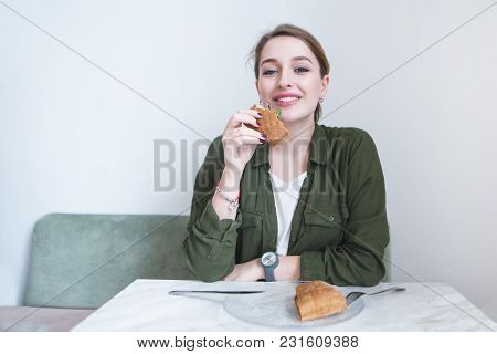 A Beautiful Smiling Woman Dancing With A Penny At The Table And Looking At The Camera. Positive Girl