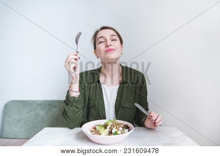 The Woman Eats A Delicious Salad. A Sweet Girl Sits At The Table, Eats A Plate Salad And Delights.