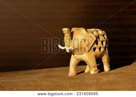Carved Wooden Figure Of An Elephant With A Trunk Raised To The Top. Toy Elephant Isolated On Dark Ba