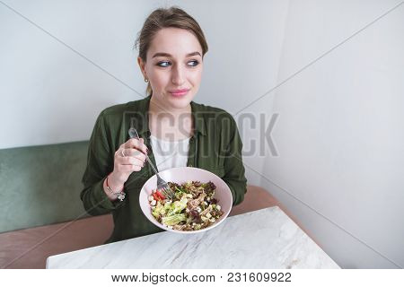 Portrait Of A Pretty Girl With A Saloote In Her Hands And A Glance In The Direction. The Woman Eats