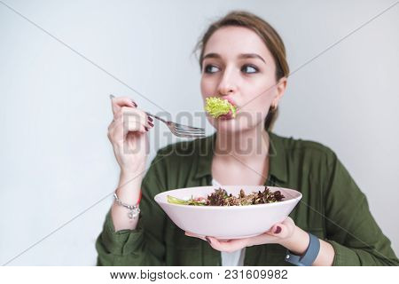 A Funny Woman Eating Salad Greens. Costume With A Plate Of Salad In His Hands. Healthy Eating And He
