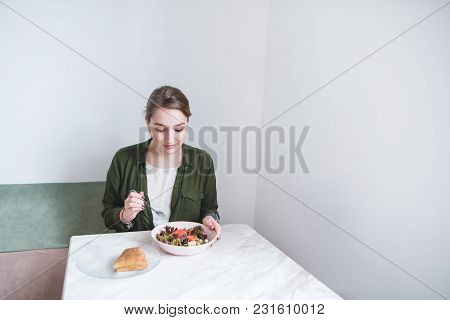 Beautiful Girl Sits In A Light Restaurant And Eats Lunch And Salad And Sandwich. Lunch At The Cafe.