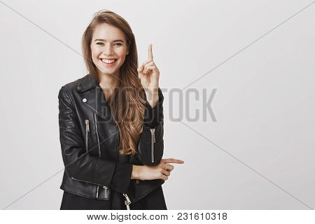 Studio Portrait Of Positive Charming Girlfriend In Leather Jacket Raising Index Finger, Pointing Upw