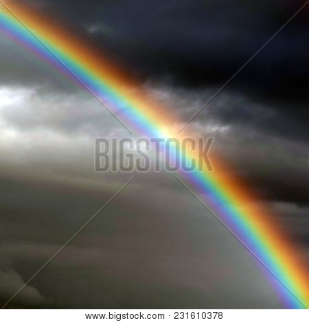 Colorful Rainbow Against A Backdrop Of Dark Clouds
