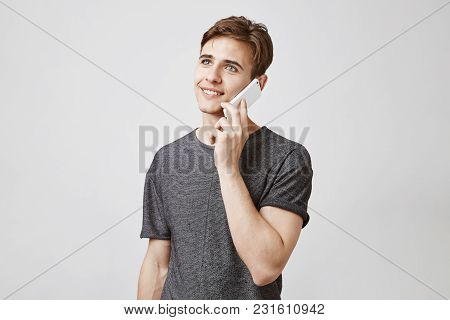 Attractive Guy With Brown Hair In A Trendy Gray Shirt Standing Near White Wall And Talking On The Ph