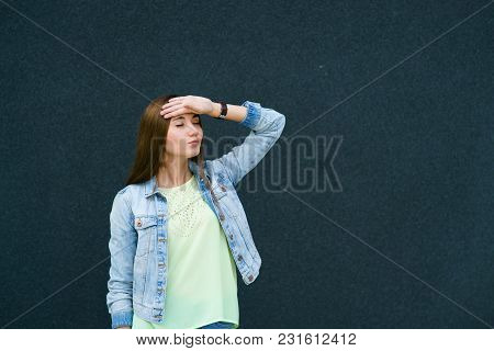 Brunette Girl In Jeans On A Dark Background Holds Her Hand Near The Forehead, Emotions