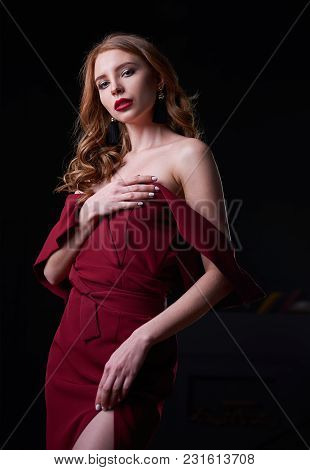 Portrait Of The Seductive Beautiful Young Woman In Lowered Red Dress