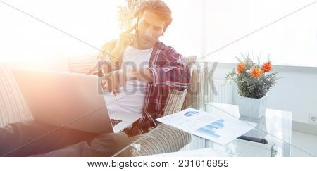 modern man working with financial documents in living room