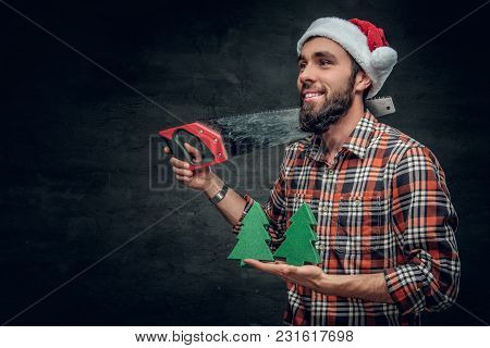 A Man In Santa's Hat Holds Small Fir Trees And Handsaw On A Shou