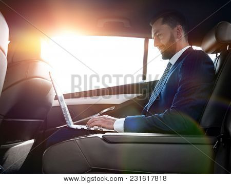 confident businessman sitting on the backseat of a prestigious car