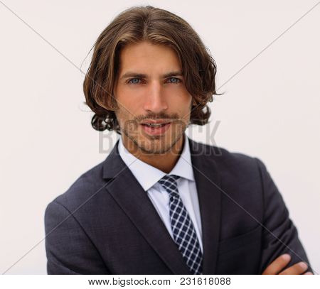 Happy young man with dark hair wearing an elegant suit