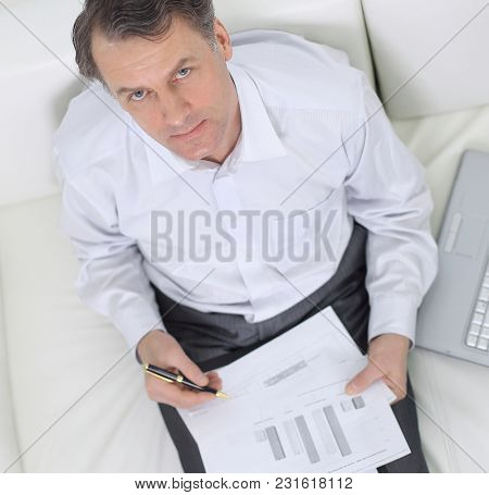 view from the top.businessman working with documents sitting on sofa