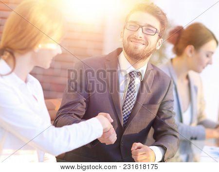 friendly handshake between colleagues in the office