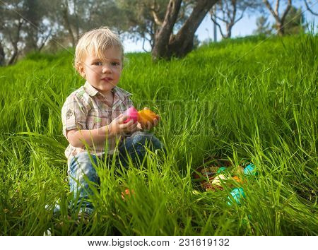 Cute Toddler With Easter Eggs In The Grass