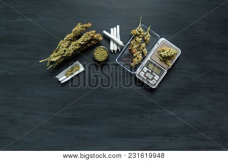 Marijuana, Scales, Jambs And A Cannabis Grinder On A Black Wooden Table Top