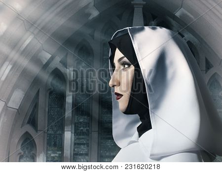 Profile View Portrait Of A Beautiful Nun In White Hooded Cloak Standing In The Church.