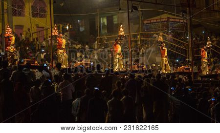 VARANASI, INDIA - MAR 13, 2018: A group of priests perform Agni Pooja (Sanskrit: Worship of Fire) on Dashashwamedh Ghat - main and oldest ghat of Varanasi located on the Ganges.