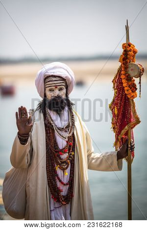 VARANASI, INDIA - MAR 14, 2018: Sadhu (holy man) on the ghats of Ganga river. Varanasi is most important pilgrimage sites in India, one of the 7 sacred cities of Hinduism.