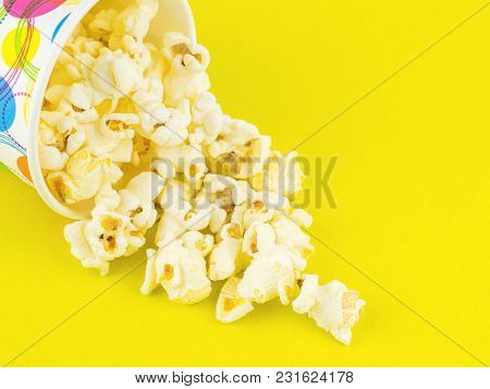 Popcorn Is Poured From A Multi-colored Paper Cup On A Yellow Table. Vegetarian Food From Corn.