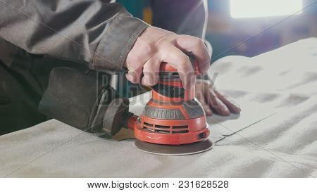 Close-up Of A Manual Sander Controlled By A Worker At The Factory And Sanding A Metal Part, Industri