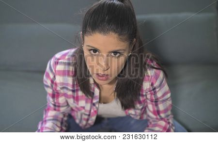 Close Up Portrait Of Young Attractive And Sad Hispanic Woman Sitting At Home Couch Looking Stressed
