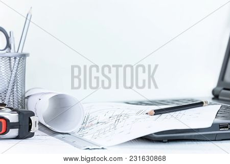 Engineering Project Plans, Measuring Tools, Pens, Laptop, On White Wooden Desk